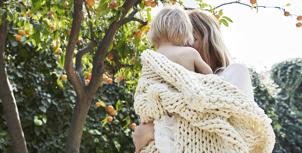 Idíl·lic jardí. Una mare i un nadó embolicats amb una manta de punt gruixut.