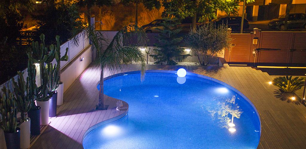 Vista general nocturna de terrassa amb piscina.